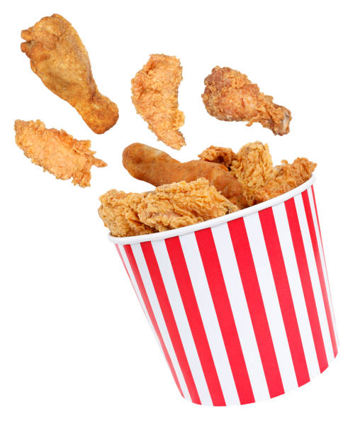 Perfect fried chicken pieces flying around in red white striped box Here are fried chicken nuggets in red white striped box. fried chicken stock pictures, royalty-free photos & images