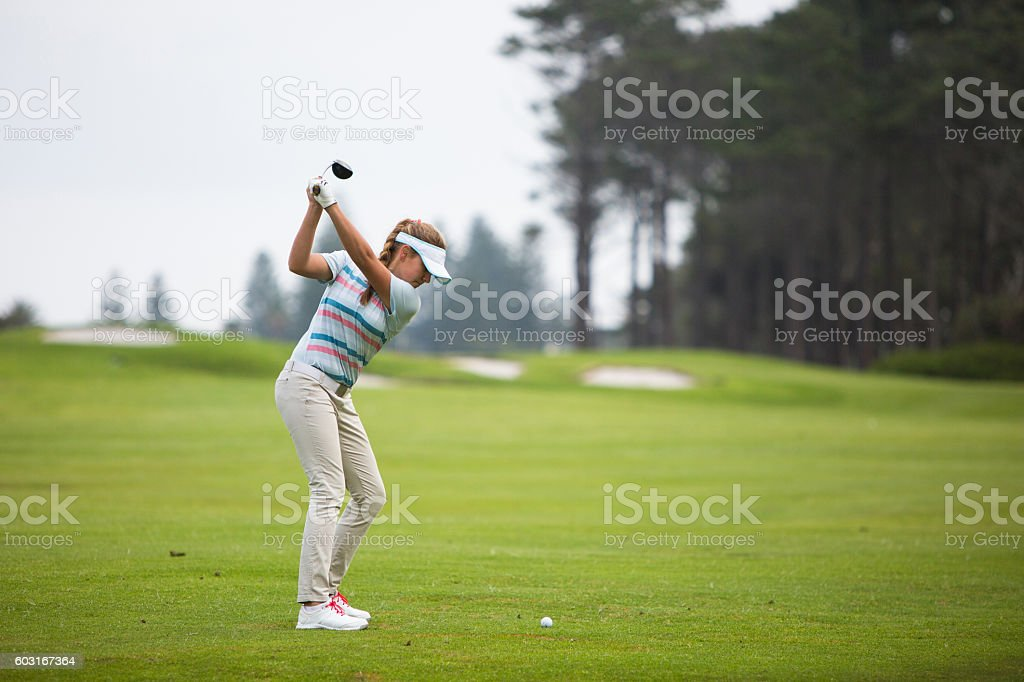 Perfect golf shot by a young female golfer stock photo
