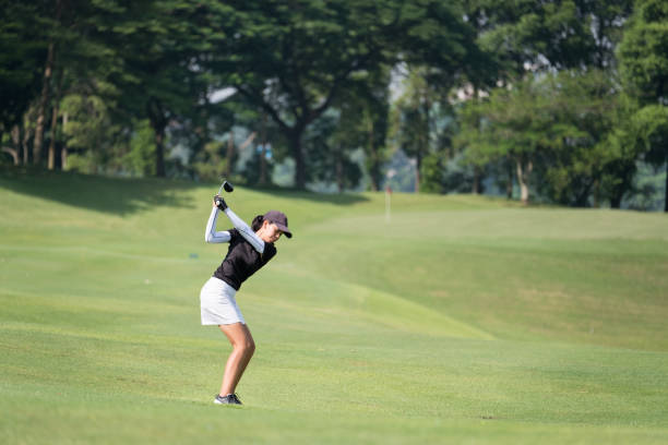 perfect golf shot - female golfer stock photos and pictures