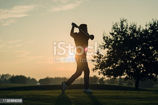 Silhouette of a golfer as he hits a perfect tee shot. Photographed against a setting sun on a course on the island of Møn in Denmark. Colour, horizontal with some copy space.