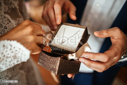 Close up of groom surprising his bride with a necklace on their wedding day.