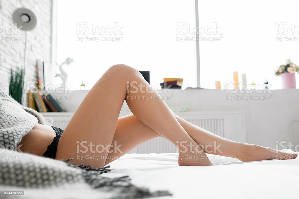 Perfect legs on bed with bent knees side view​​​ foto