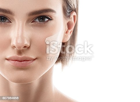 istock Perfect makeup. Skin tone cream lines on woman face. 607984658