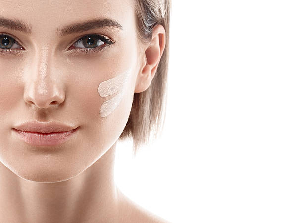 Perfect makeup. Skin tone cream lines on woman face. Skin tone cream lines on woman face. Beautiful woman portrait beauty skin healthy and perfect makeup. Studio shot. Isolated on white. toned image stock pictures, royalty-free photos & images