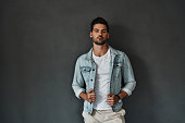 Handsome young man looking at camera and adjusting his denim jacket while standing against grey background
