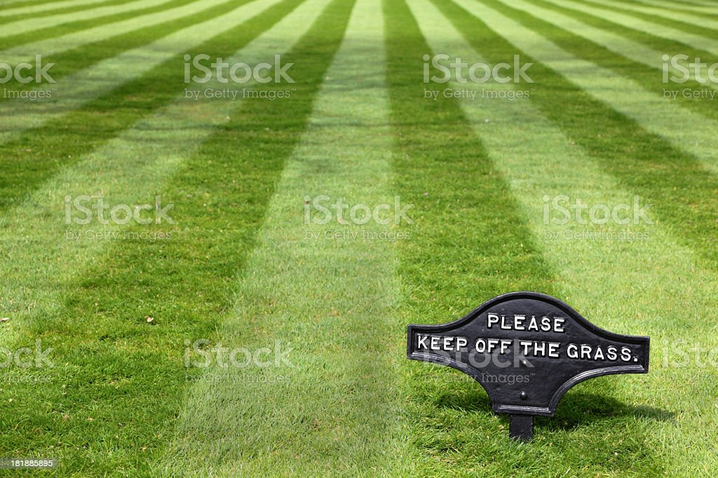 perfect manicured lawn with keep off the grass sign stock photo