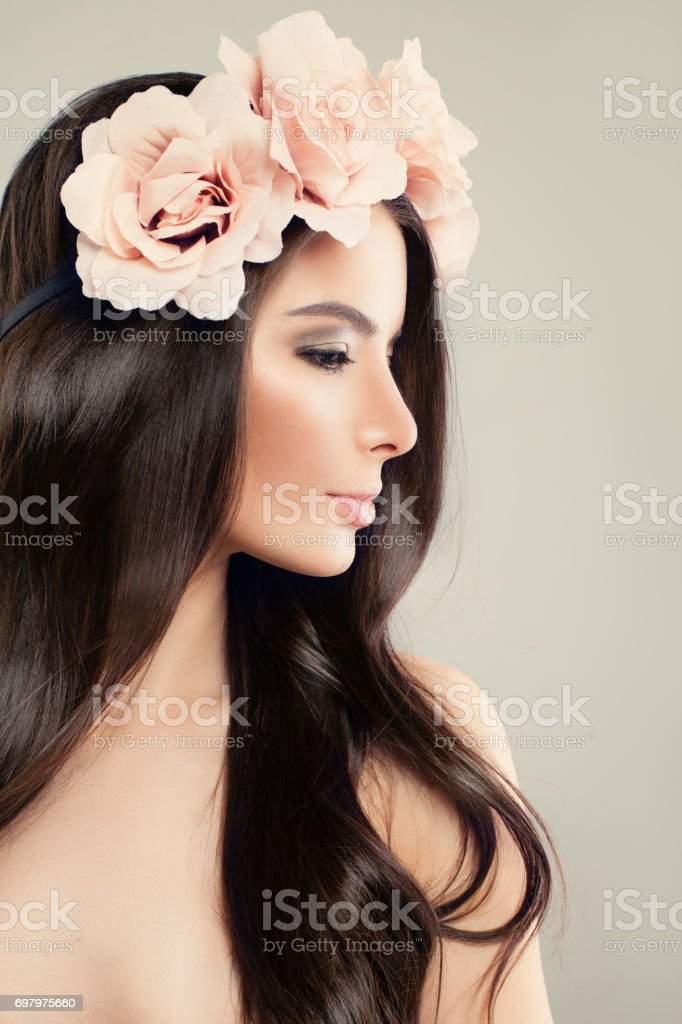 Perfect Model Woman with Summer Pink Flowers. Long Healthy Hair and Makeup stock photo