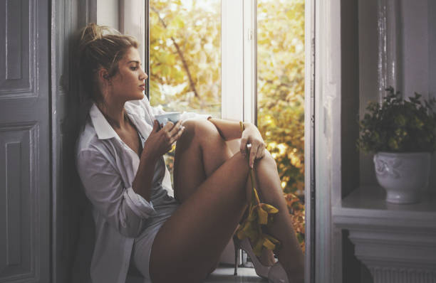 Perfect morning by myself. Closeup side view of attractive blond woman sitting by a window and having a coffee. She's wearing underwear and her boyfriend's white shirt. Looking throigh the window and enjoying this peaceful morning. Toned image. lingerie stock pictures, royalty-free photos & images