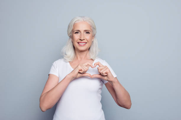 Perfect, nice, aged, old, pretty woman, lover in t-shirt making, showing heart figure with fingers, looking at camera, celebrating woman's day, standing over gray background stock photo