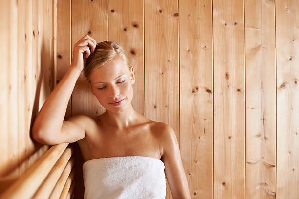 Perfect Peace A gorgeous blond woman relaxing in a sauna sauna stock pictures, royalty-free photos & images