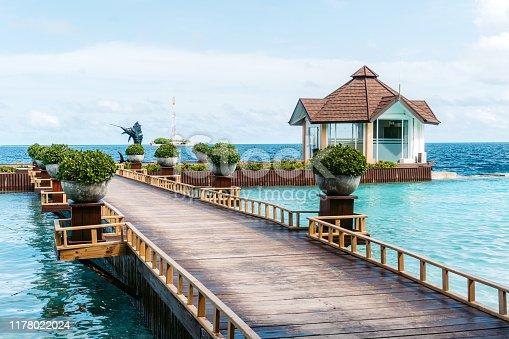 Boardwalk connecting seashore and small beach hut at sea.