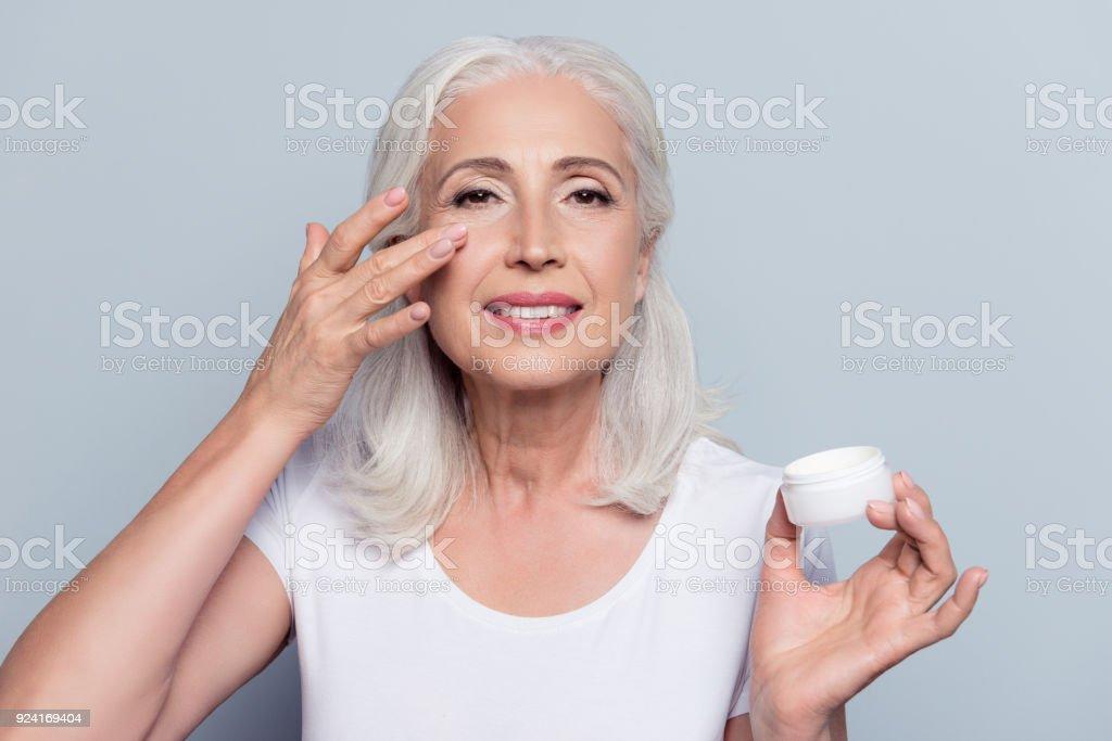 Perfekt, hübsch, Frau Augencreme auftragen, hält Glas Kosmetikums Blick in die Kamera über den grauen Hintergrund – Foto