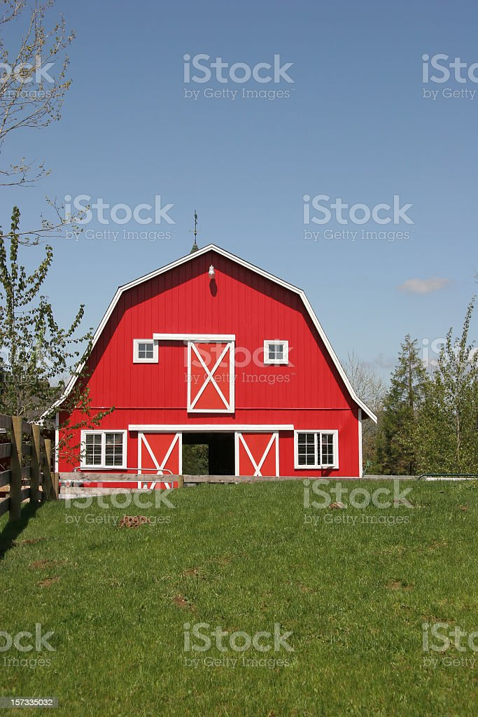 Perfect Red Barn With Bright Blue Sky And Green Grass stock photo