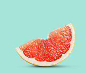 Perfect red grapefruit slice on pastel green. This file is cleaned, retouched and contains clipping path.
