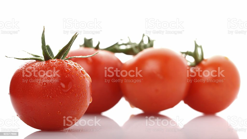 perfect red wet tomato with three tomatoes on background royalty-free stock photo