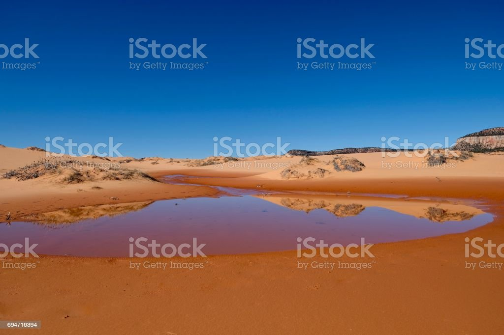 Perfect reflection of sand dunes in calm water. stock photo