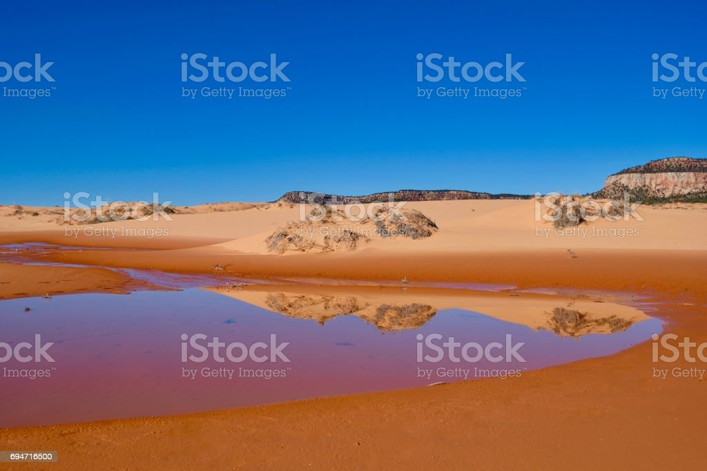 Perfect reflection of sand dunes in calm water stock photo