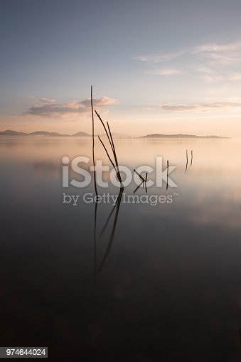 Perfect reflections of a dusk on the lake, with clouds and hills reflecting on water, soft and warm colors, and some wooden poles coming out of water