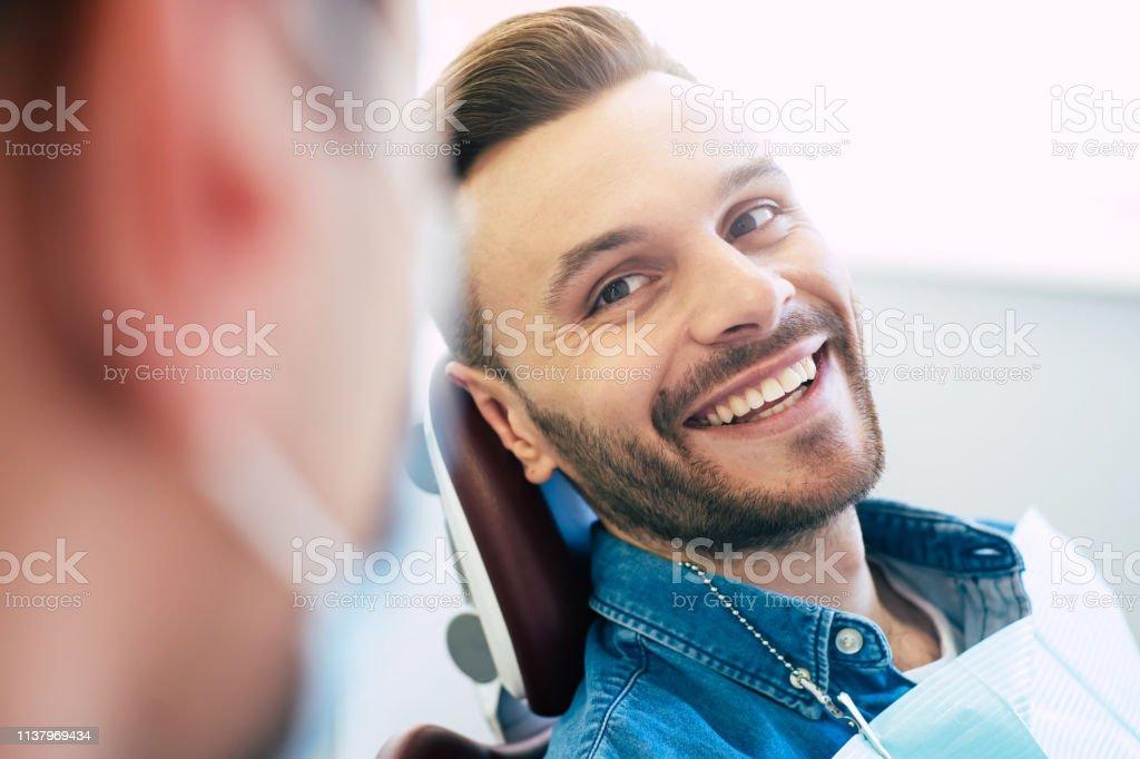 Ein perfektes Ergebnis der Arbeit eines Zahnarztes, das sich im schönen und weißen Lächeln eines Patienten zeigt, der mit einem Ergebnis einer Behandlung in einer Klinik absolut zufrieden ist. - Lizenzfrei Arzt Stock-Foto