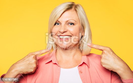 Beautiful happy blonde senior woman is pointing on her toothy healthy smile and looks on camera