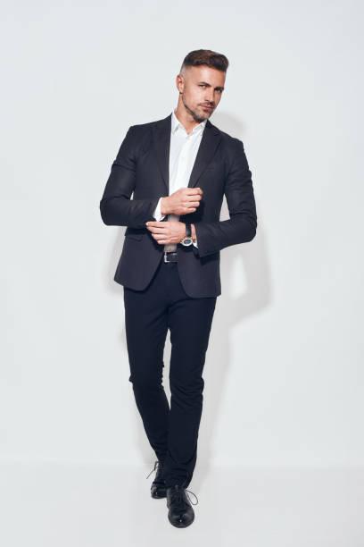 完璧なスタイル。古典的なスーツでハンサムなひげを生やしたビジネスマンのフルレングスは、袖を調整し、灰色の背景に立ちながらカメラを見て - ジャケット ストックフォトと画像