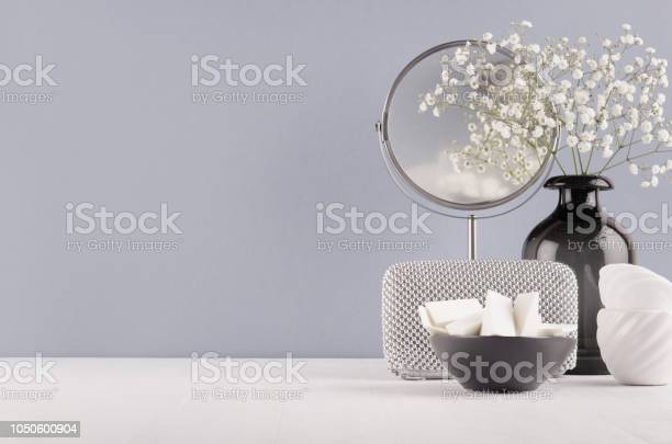 Photo of Perfect stylish decoration for home in grey colors - black glass vase with small fluffy flowers, mirror, female silver cosmetic bag, bowl sponges on soft ligth white wood table.