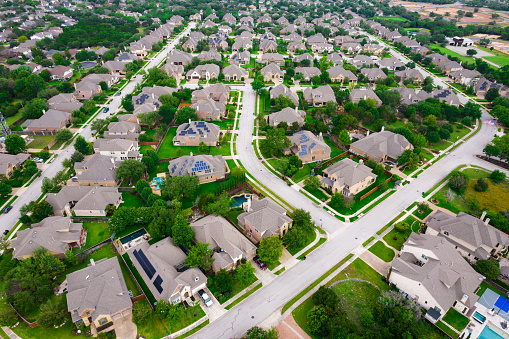 Perfect Suburb curved modern streets Row after row of thousands of nice large two story houses Aerial Drone view above Luxury living gated community Suburb in Austin Texas USA green summer landscape in Round Rock , TX