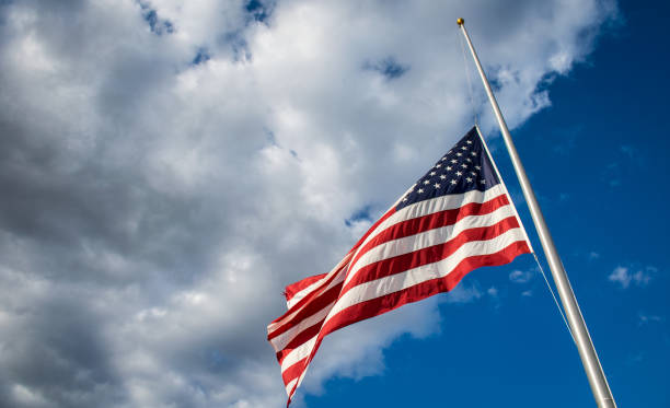 Perfect Sunshine American Flag lowered to Half-Mast flag flying to the left stock photo