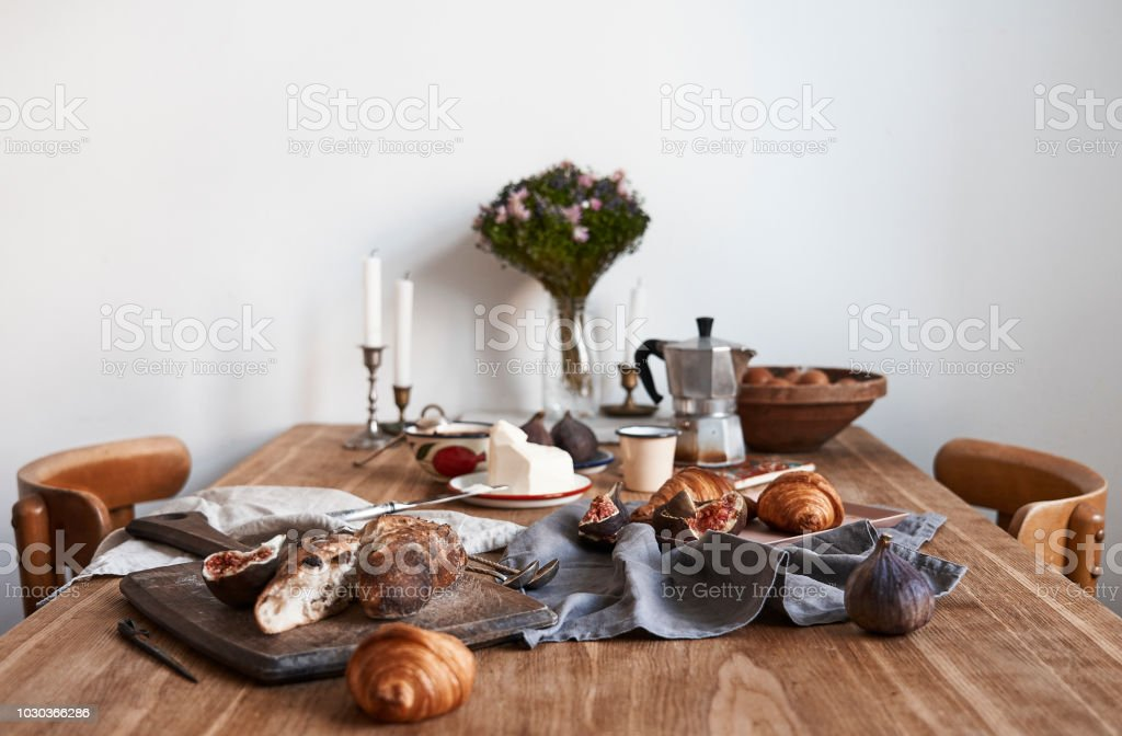 Perfect tasty provence breakfast on wooden table in white kitchen interior, empty white wall, daylight