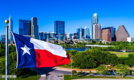 istock Perfect Texas flag flying in front of Austin Texas downtown skyline cityscape sunny perfect day 821679198