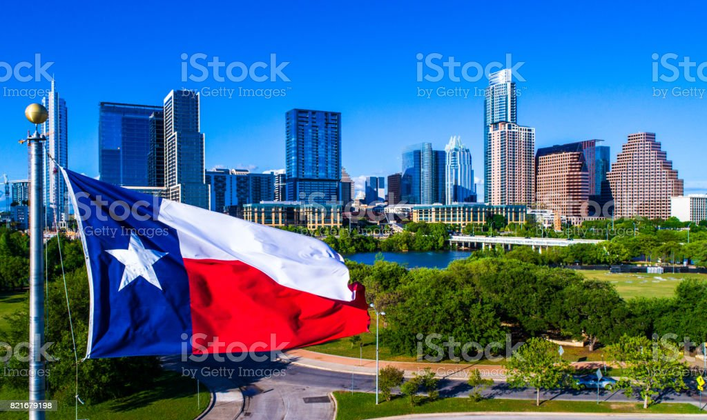 Perfect Texas flag flying in front of Austin Texas downtown skyline cityscape sunny perfect day stock photo