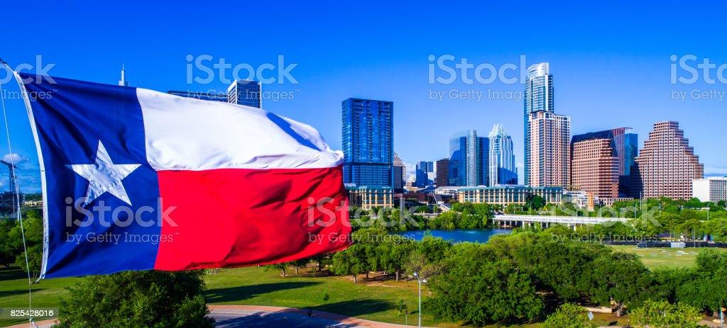 Perfecta bandera de Texas ondeando en el viento frente a Austin Texas paisaje de horizonte amplio - foto de stock