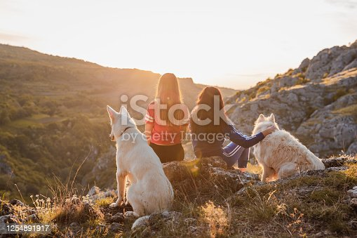 Two females sitting on the rock with their white dogs watching the sunset in the mountains.