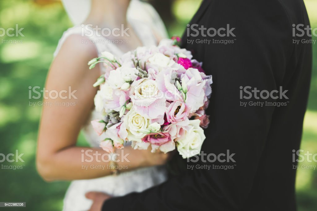 Perfect wedding couple holding luxury bouquet of flowers stock photo