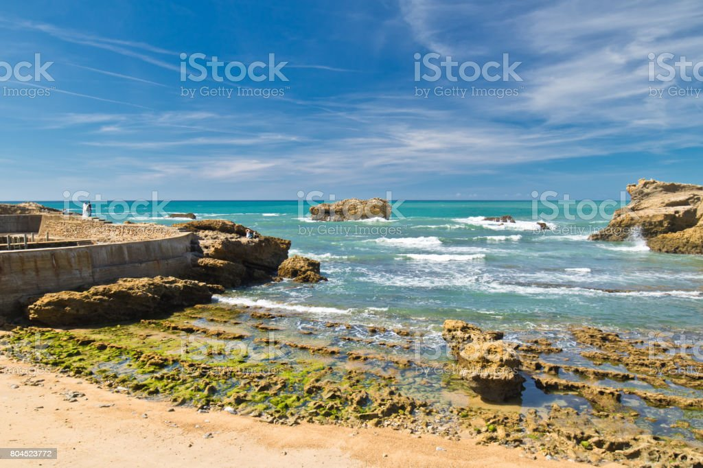 perfect wedding of bride and groom standing on rock on scenic colourful atlantic coast in blue sky in biarritz, basque country, france stock photo