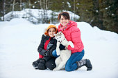 Shot of a mother and son with their pet husky dog in snow outdoors