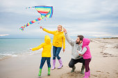 Young Family Flying Kite On Beach