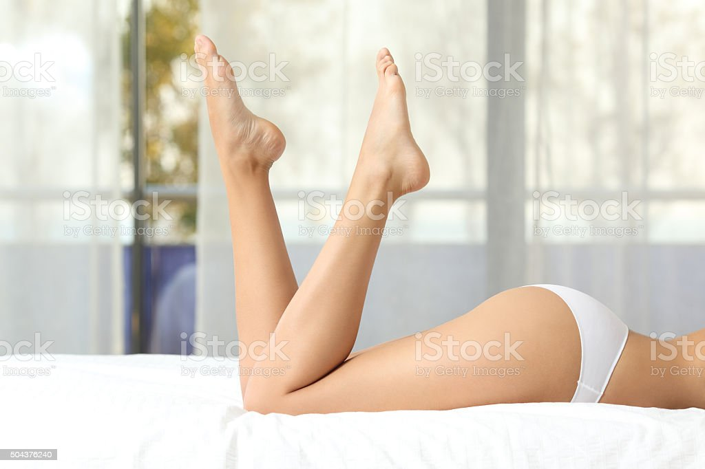 Perfect woman waxed legs on a bed stock photo