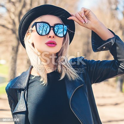 Perfect young woman outdoors. Female model face, girl in black hat
