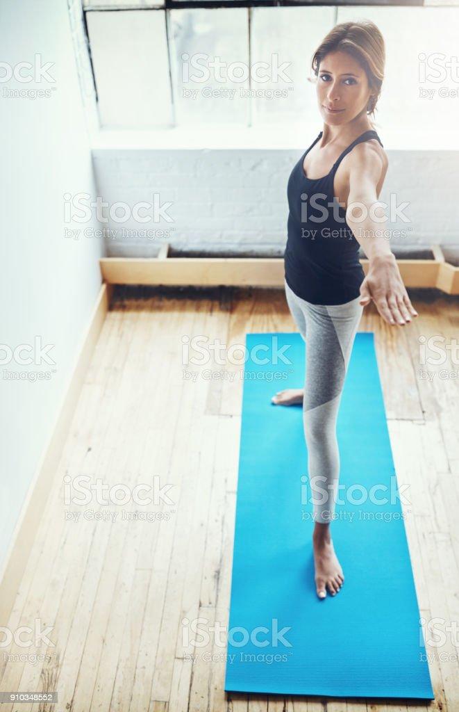 Perfecting her posture through yoga stock photo