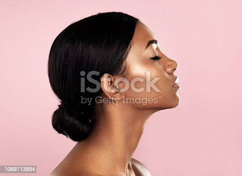 Studio shot of a beautiful young woman posing with her eyes closed against a pink background