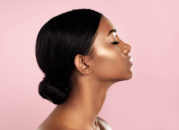 Perfection in profile Studio shot of a beautiful young woman posing with her eyes closed against a pink background side view stock pictures, royalty-free photos & images