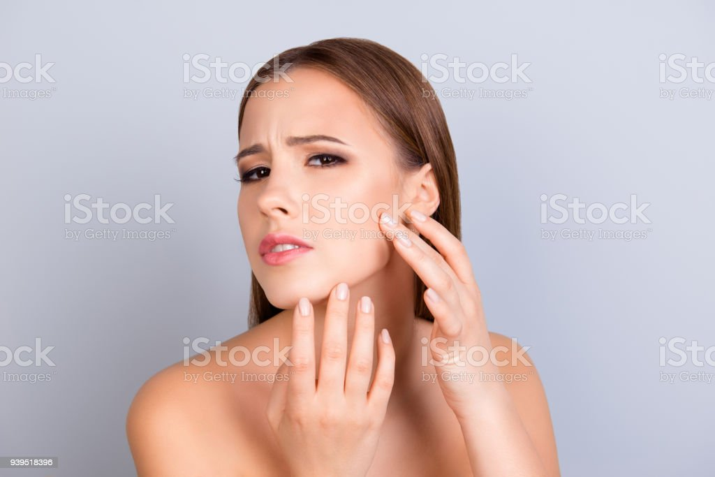 Perfection is a hard work. Acne, pimple, clear and clean, oily, dry  skin concept. Cose up cropped photo of worried young lady touching her face gently stock photo