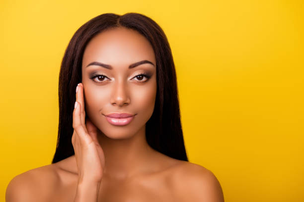 Perfection is a hard work! Pampering, pimple, wrinkle, clear and clean, oily, dry skin concept. Cose up cropped photo of afro gorgeous charming brunette touching gently her ideal face stock photo