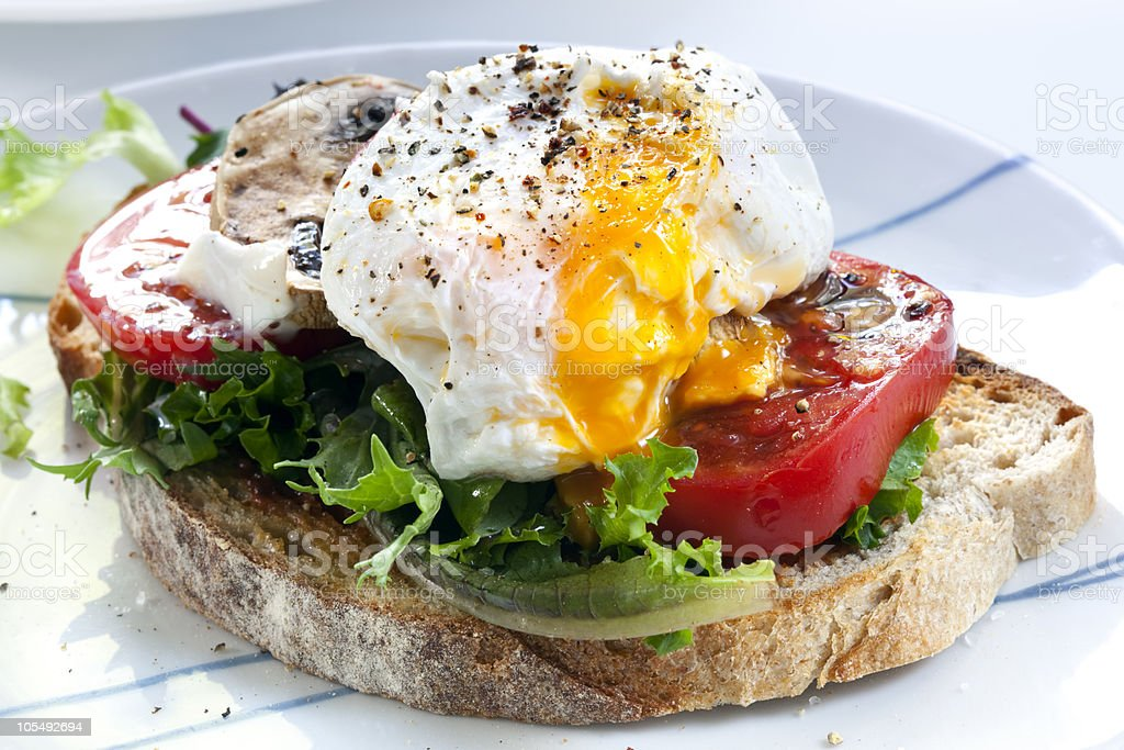 Perfectly done poached egg on toast with tomato and lettuce stock photo