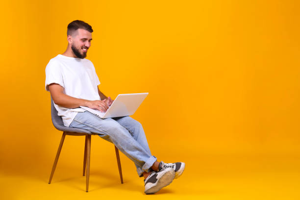 perfectly groomed bearded man with fashionable hairstyle posing over yellow background. - remote work imagens e fotografias de stock