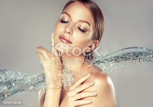 1070715740 istock photo Perfectly looking model surrounded by flying water stream. Cosmetology and skin care. 1070715732