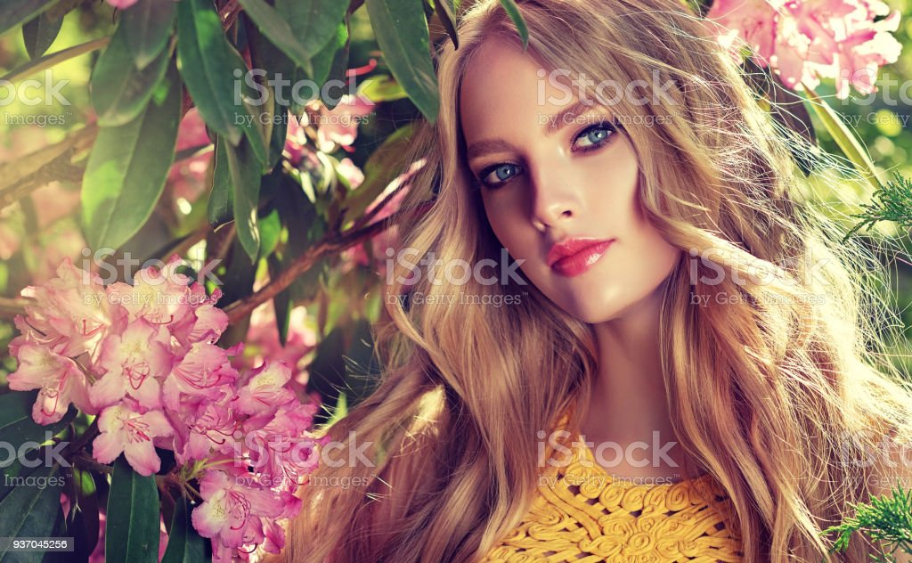Perfectly looking young woman is gazing on the viewer.  Spring blossom and bloom of youth. Symbol of blooming youth.