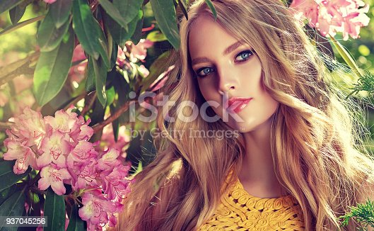 Magnificent young woman surrounded by blossoming flower trees. Gentle makeup, rose lipstick and freely lying long hair curls. Spring style. Spring blossom and bloom of youth.