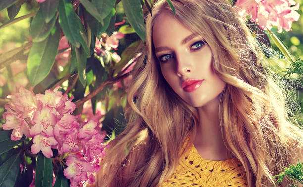 perfectly looking young woman is gazing on the viewer.  spring blossom and bloom of youth. symbol of blooming youth. - makeup fashion stock pictures, royalty-free photos & images